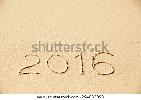 2016 inscription written in the wet yellow beach sand. Concept of celebrating the New Year at some exotic place - stock photo