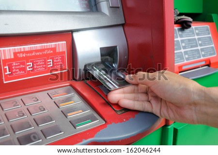 inserting card into an ATM to begin a financial transaction - stock photo