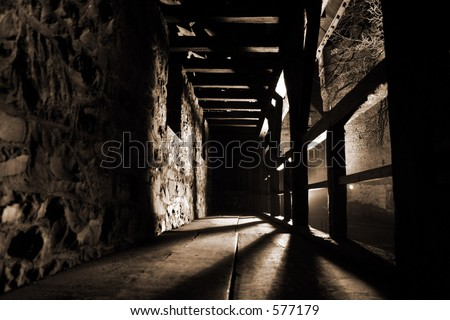 Inside view of a defensive walkway along the outside walls of the city castle of Altena at night. Strong light and shadows give this image a daunting and mysterious atmosphere. - stock photo
