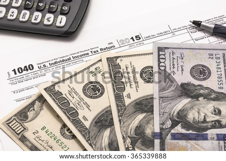2015 Internal Revenue Service form 1040 close up detail with United States currency, black pen and calculator. Tax season is January to April.  - stock photo