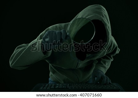 Internet Theft - a man wearing a balaclava looking at computer screen using magnifying glass  - stock photo