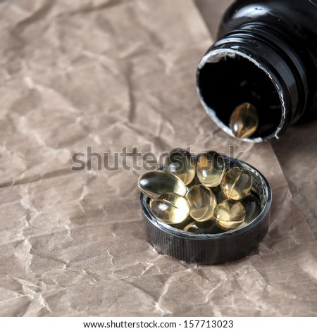 Inverted black bottle with  capsules,  closeup