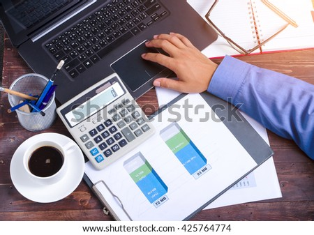 investment consultant analyzing company annual financial report balance sheet statement working with documents graphs - stock photo
