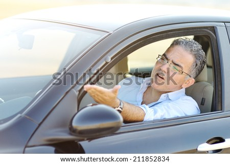 irritated male driving his car in traffic - road rage concept - stock photo