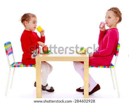 2 is a cheerful little girls play in a restaurant with table- isolated on white background - stock photo