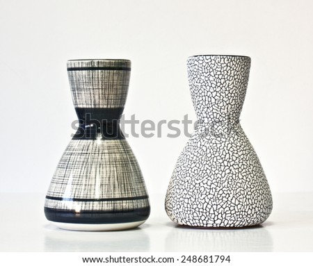 Israeli ceramic pair in black and white : two vases of 1950-th years. Glazed surfaces, contrast details. Symbolizes couple: He and She; brother and sister, bride and groom etc. Isolated on white.
