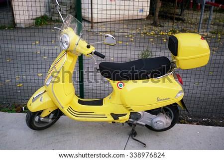 ISTANBUL, TURKEY - NOVEMBER 14, 2015:New yellow Vespa Italian designed scooter is parking on street along the sea at NOVEMBER 14, 2015: in istanbul,Turkey - stock photo