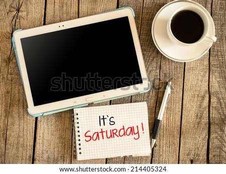 "It""s Saturday. Tablet PC, cup of coffee on wooden background,Its Saturday text on small notepad - stock photo"
