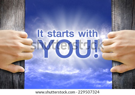 """""""It starts with YOU"""" text floating in the Sky while 2 hands opening a wooden door. - stock photo"""
