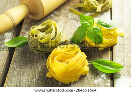 Italian pasta with fresh basil on the wooden surface. Selective focus  - stock photo