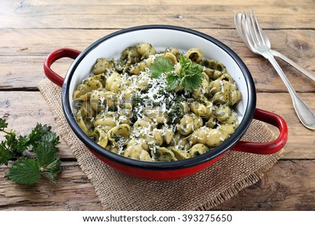 italian pasta with stinging nettles in metal pan rustic kitchen table background