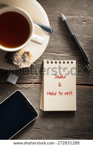 """Jaded & need to rest"" is written on small notepad with a cup of tea, pen, pencil and cellphone on rustic wood background with low key scene"