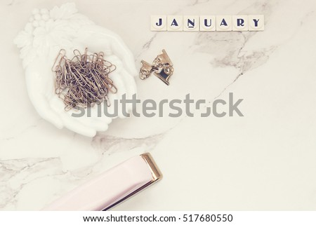 """January"" printed on tiles. Over head flat lay view of desktop. Pink stapler, white hands dish, gold paper clips. Open space against marble background."