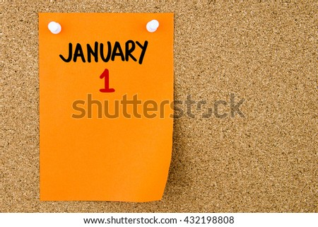 1 JANUARY written on orange paper note pinned on cork board with white thumbtacks, copy space available - stock photo