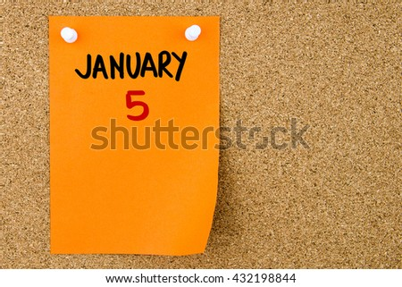 5 JANUARY written on orange paper note pinned on cork board with white thumbtacks, copy space available - stock photo
