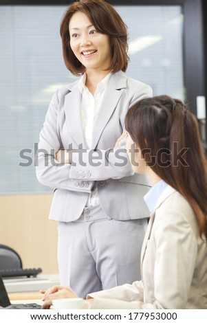 2 Japanese Business women talking in the office