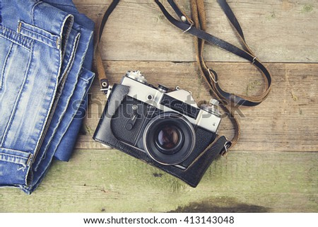 jeans   and camera on wooden background - stock photo