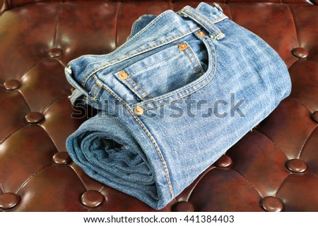 Jeans folded on the leather sofa.