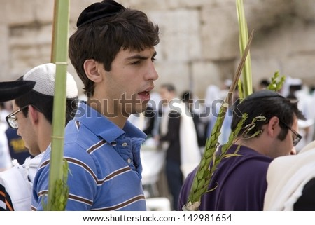 JERUSALEM-October 02: The Jews at the Western Wall during Jewish holiday of Sukkot, October 2, 2012 in Jerusalem, Israel.Etrog and Lulav is two of four species used during of Sukkot. - stock photo