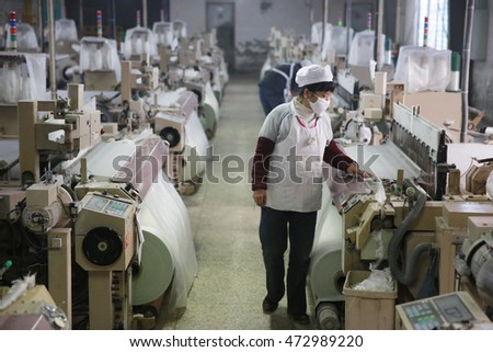 Jiangxi,CHINA -January1, 2014: the company workers operating machinery to produce new glass fiber products. which export to European Union.