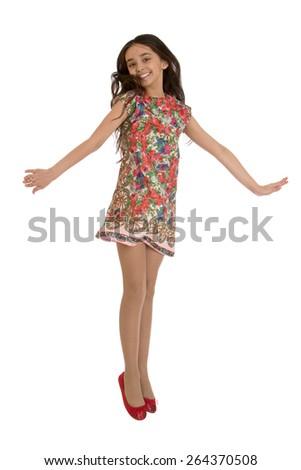 Joyful girl in colorful dress jumps- isolated on white background - stock photo