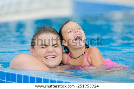 joyful happy smiling kids swim and play in outdoor swimming pool - stock photo