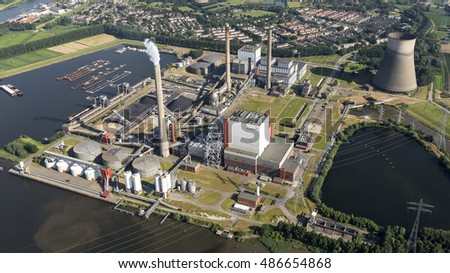 19 July 2016, Geertruidenberg, Holland. Aerial view of the AMERCENTRALE, a coal and biomass fired Essent powerplant. It's located at the river Amer. In the back the town of GEERTRUIDENBERG.