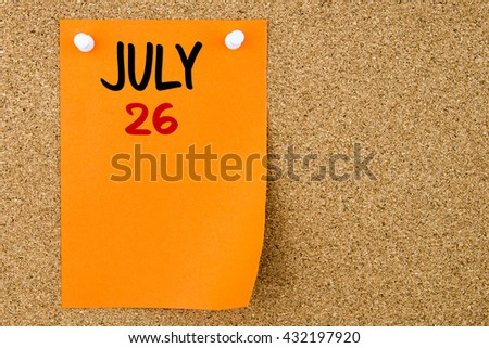 26 JULY written on orange paper note pinned on cork board with white thumbtacks, copy space available - stock photo