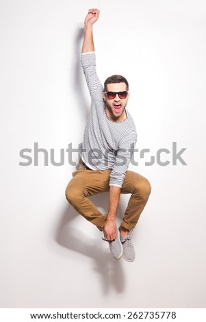 Just having fun. Excited young man jumping in front of the white wall and keeping mouth open  - stock photo