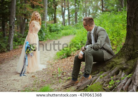 Just married loving hipster couple in wedding dress and suit in green forest at sunset. happy bride and groom posing near the old terr in the summer wood. Romantic Married young family in the park - stock photo