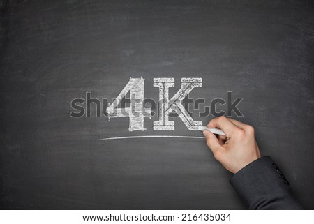 4K technology concept on black blackboard with hand - stock photo