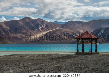 Kashmir Pavilion with pray flag stand alone at Pangong lake with beauty view surrounded by mountain range and turquoise colour lake.   - stock photo