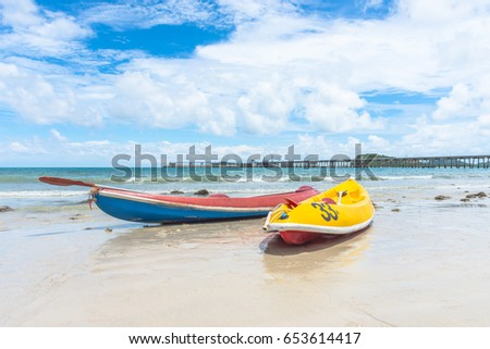 kayak or canoe on the seaside sand beach background  white cloud blue sky and bridge pier