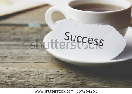 key with success and coffee on wooden table