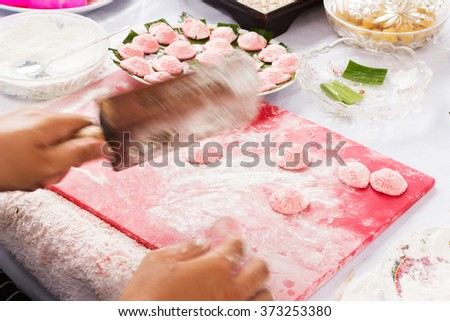 'Khanom Tao' or the red turtle dessert is used in the Pho To Festival in Phuket, Thailand; made from wheat and sugar in red turtle shape represents good luck and longevity. (motion blur) - stock photo