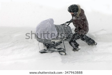 Kholmsk, Sakhalin Island, Russian Federation, 7 January 2015. Father unidentified rolls the child in a baby carriage through the snowdrifts in a strong snowstorm. - stock photo