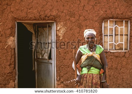 KIBUYE, RWANDA, AFRICA - SEPTEMBER 11, 2015: Unknown woman. She looks into camera in front of her earthen house. Only her baby's feet appears. There is no glass on windows and doors of her house.