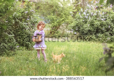 Kid girl walking with cat in the spring garden with lilac flowe