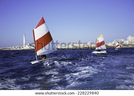 Kids learn to sail Optimist dinghies - stock photo