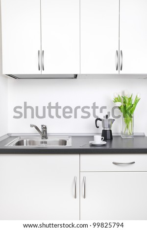 Kitchen interior, cup of coffee, percolator and tulips on worktop - stock photo