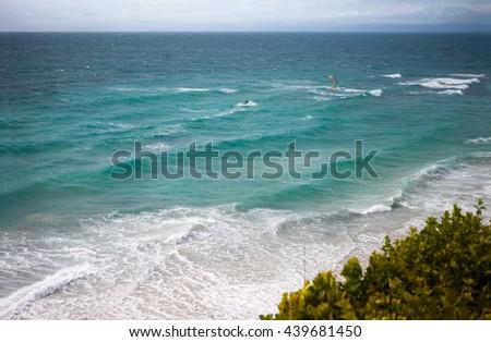 Kite surfer enjoying in waves on sea  - stock photo