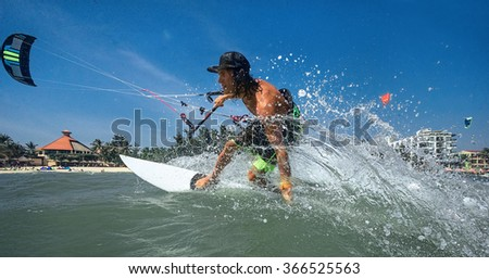 Kitesurfer with board on ocean wave