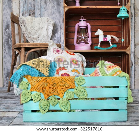 knitted home decorations in wooden box on retro interior background - stock photo