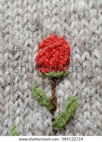 Knitted red flower on a gray sweater - stock photo