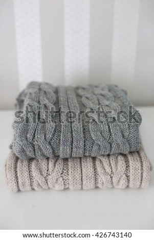 Knitted wool winter hat, scarf on the white table - stock photo