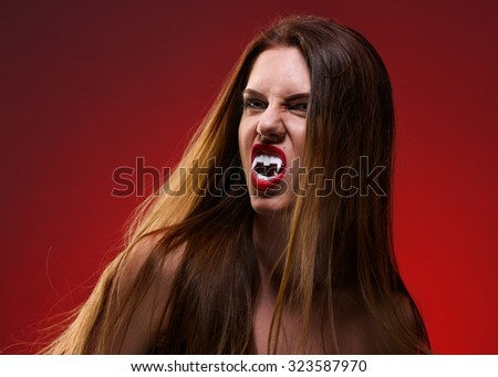 Lady Vampire Style. Portrait of Brunette Woman over red background.