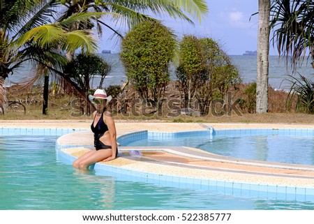 Lady with swimsuit show shape on pool,  in Chumphon province Thailand.