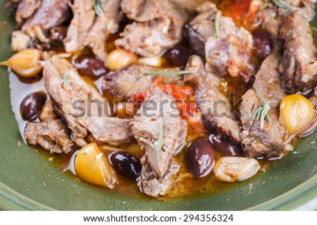 Lamb meat cooked in a tagine with olives, garlic, lemon and rosemary. - stock photo