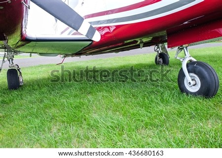 Landing gear of small plane on green grass.