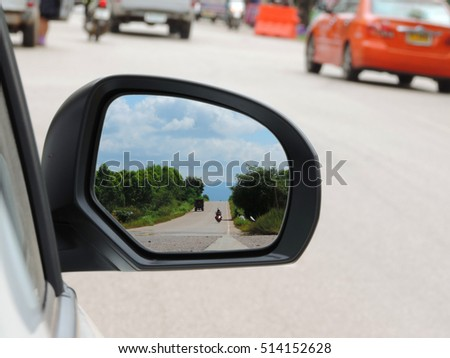 landscape reflected in the rear view mirror of car.